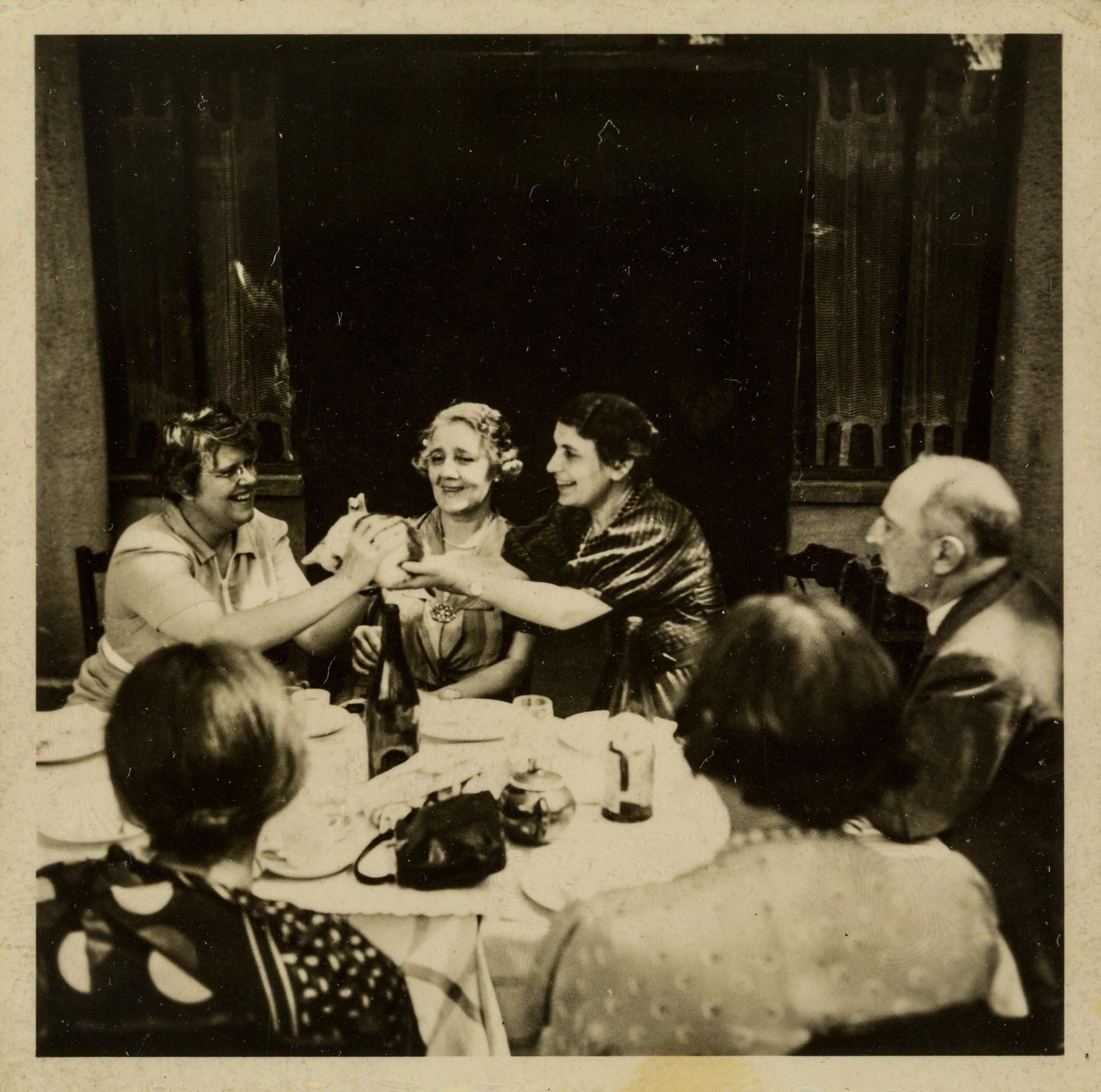 Melanie Klein avec Anna Freud, Ernest Jones et d'autres assis autour d'une table et se passant un chaton