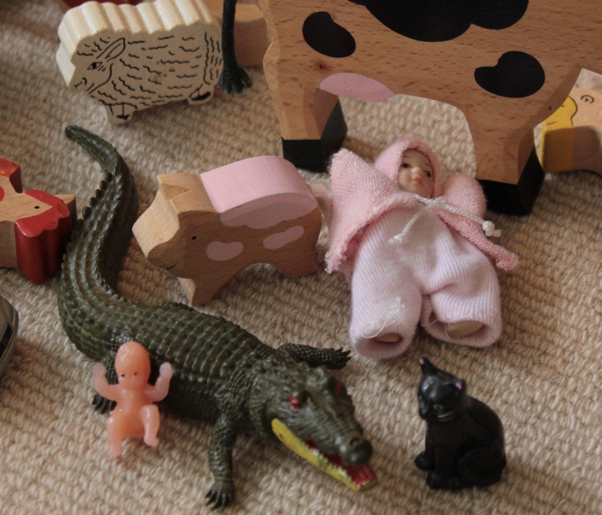 Современные игрушки, включая маленьких куколок и деревянных и пластмассовых зверей