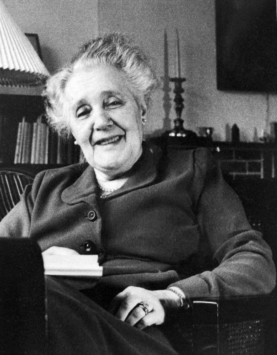 Black and white photograph showing Melanie Klein in 1957, seated in a living room, smiling